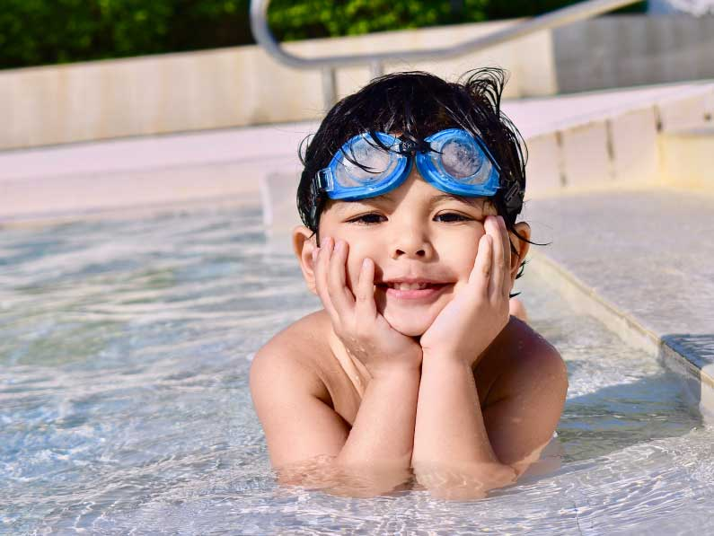 Happy little boy posing in pool.