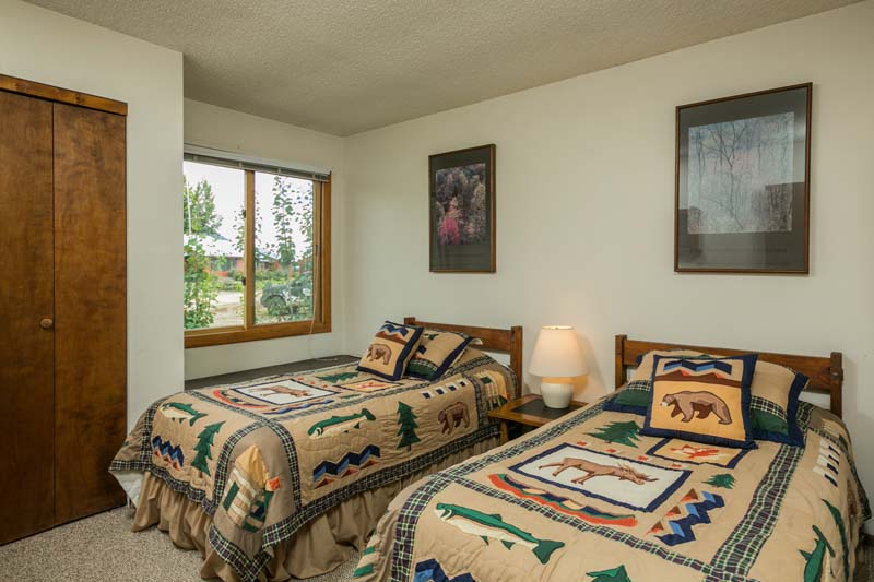 Big Horn cabin bedroom with two twin beds and a window seat.