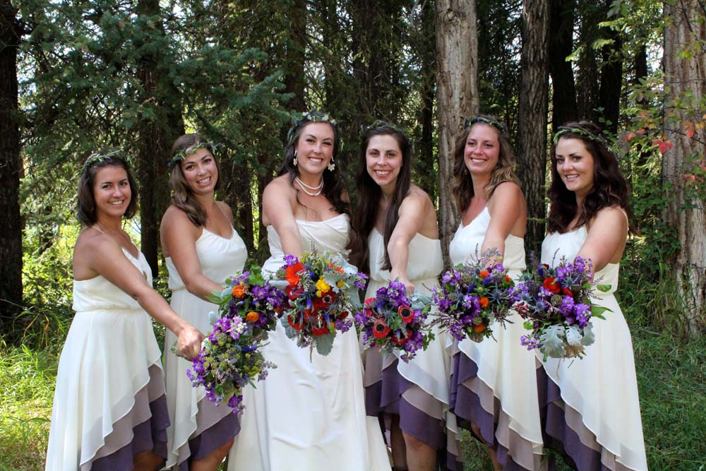 Bride and bridesmaids showing off their flowers with treed background.