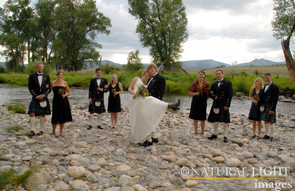 Wedding party posing on the rocky shore of the Elk River.
