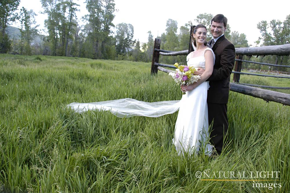 Bride and Groom posing next to fencing in a grassy field.