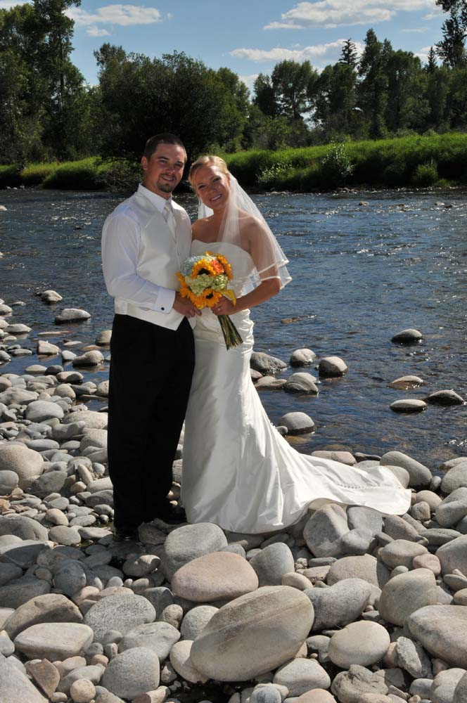 Groom and bride posing on rocks in front of Elk River.