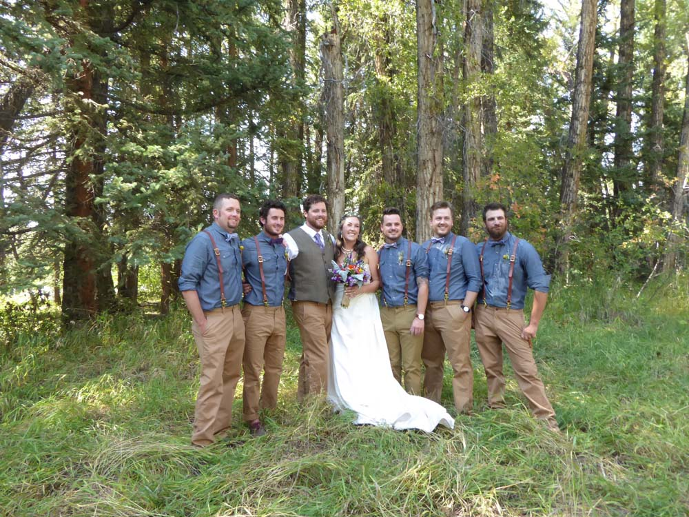 Bride and Groom posing with groomsman in a feild.