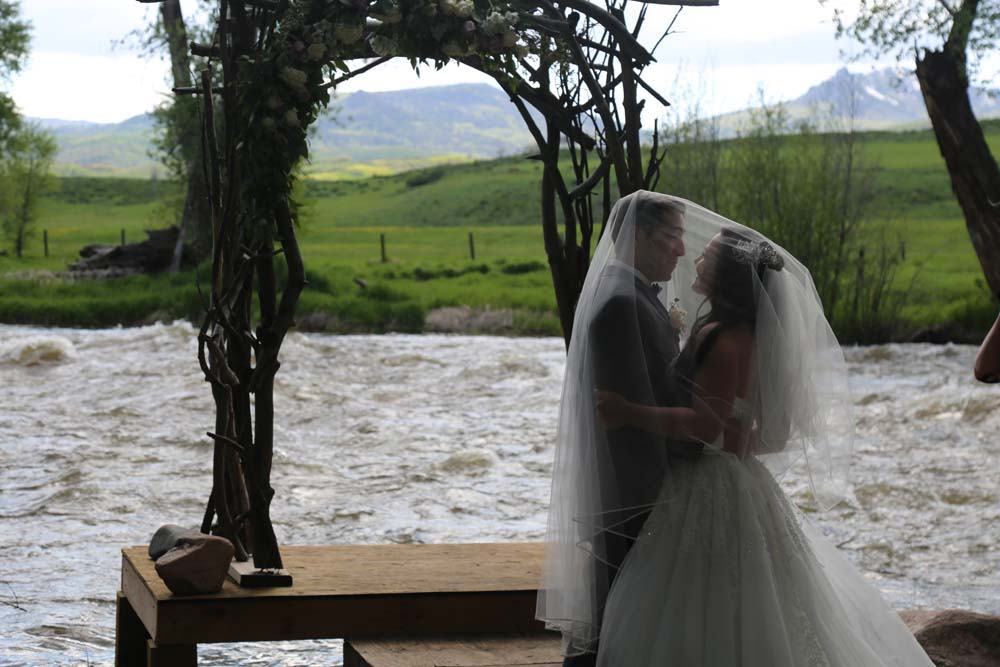 Bride and Groom under the bride's veil at the ceremony site with the Elk River in the background.