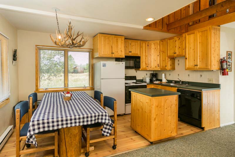 Hiker cabin full kitchen with small island bar and large rectangle table.