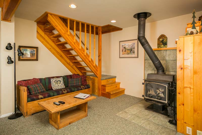 Hiker cabin living room with fire stove and stairs.