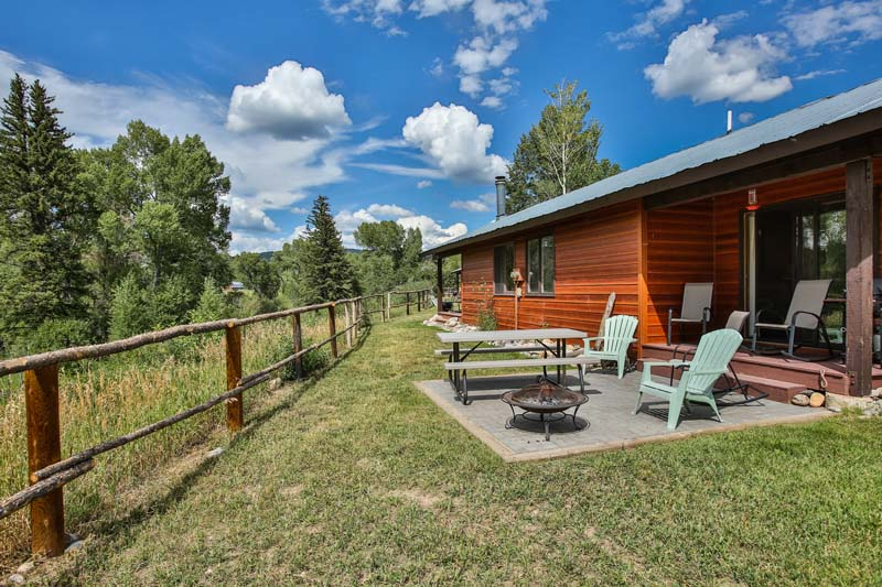 Outside view of Fishhook cabin patio area with fire pit and picnic table.