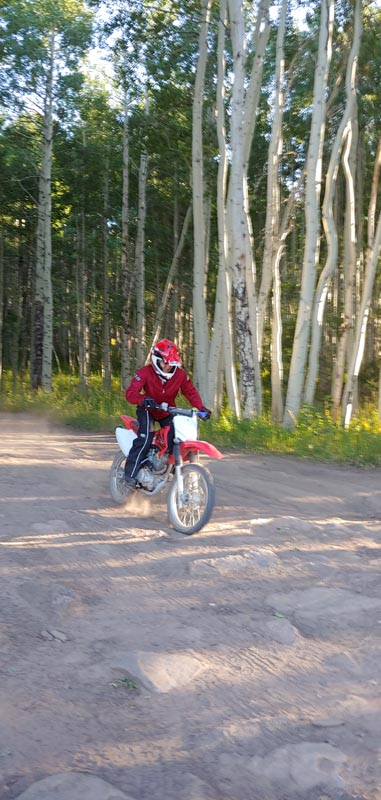 Motorcyclist heading down the trail with aspen trees