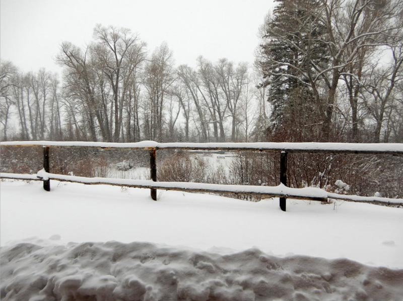 Snow covered fence with Elk River in the background.