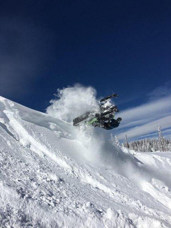 Man jumping a snowmobile in fresh powder.