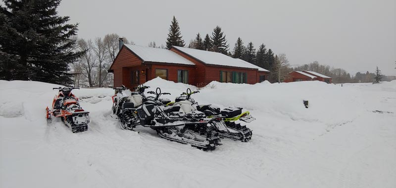 Snowmobiles parked in front of cabin.