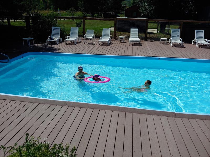 Parents enjoying the pool with their child.