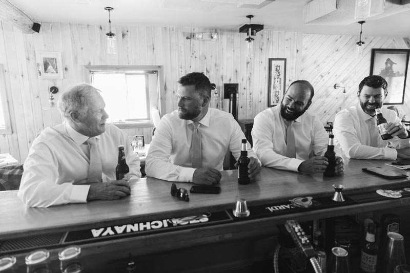 Groom along with groomsman and father enjoy a beer in the restaurant before ceremony.