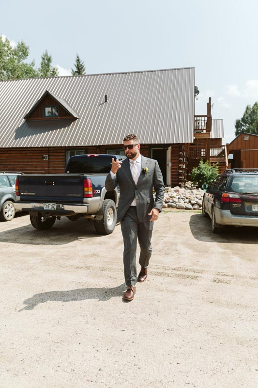 Groom exiting the restaurant in parking lot.