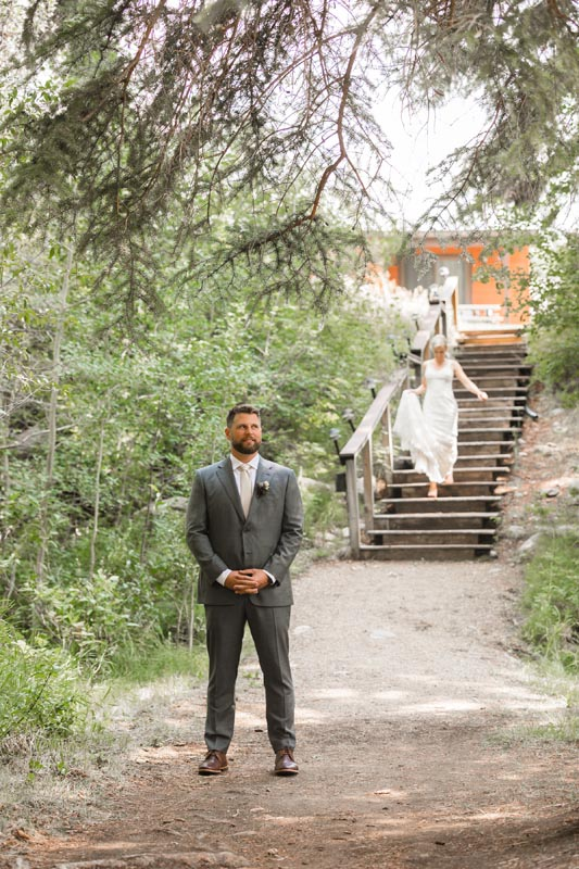 Groom awaiting his bride coming down the stairs from cabins for their first look.