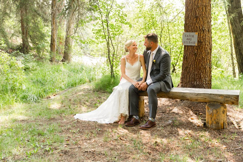 Bride and Groom enjoy a moment on bench down by river.