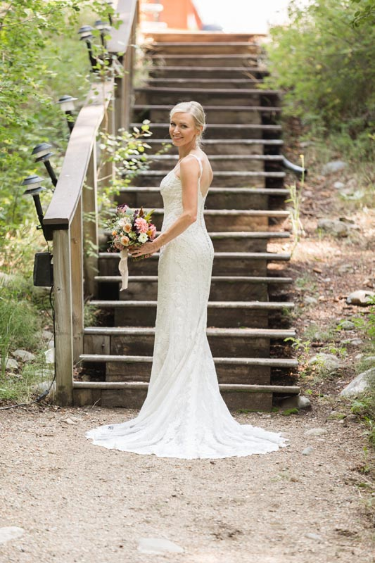 Bride portrait in front of stairs that lead to guest cabins.