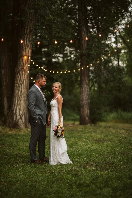 Groom and Bride standing in field with twinkle lights.