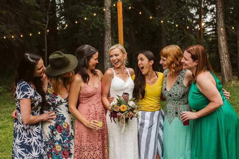 Bride laughing with friends in field with twinkle lights.