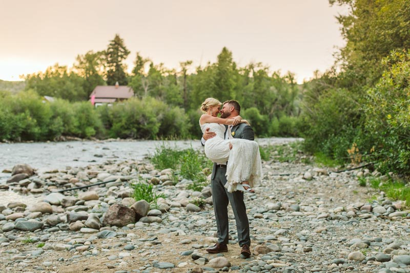 Groom holding bride on the bank of the Elk River at sunset.