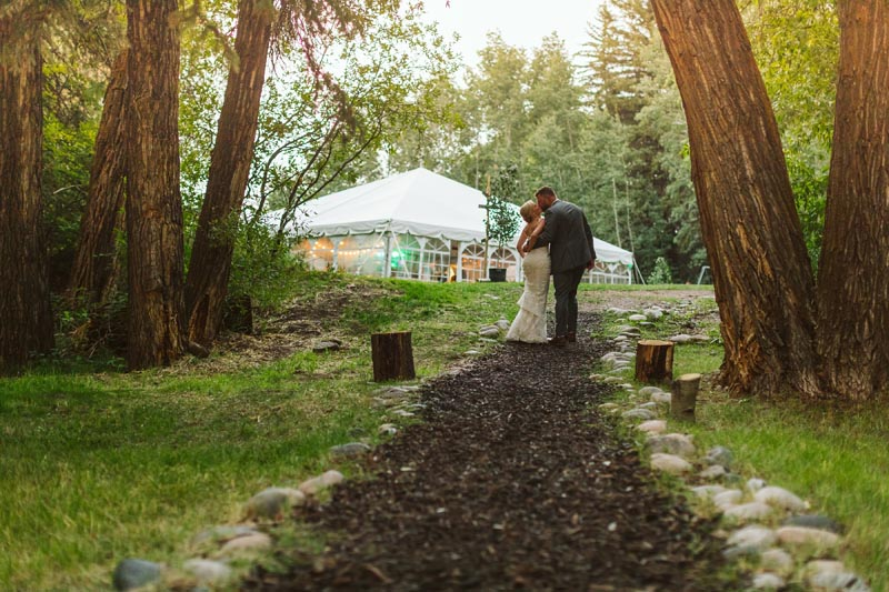 Bride and Groom kissing on path with reception tent in background.